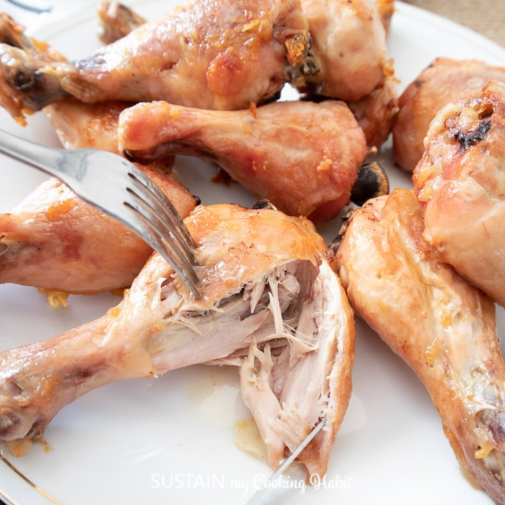 A fork piecing a piece of tender and juicy chicken drumsticks