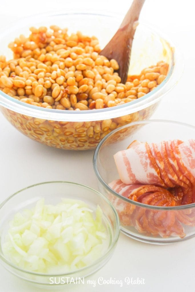 navy beans with sauce next to a bowl with onions and bacon.