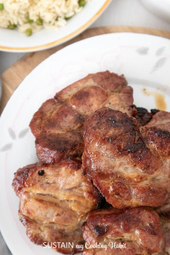 Close up of grilled pork shoulder pieces.