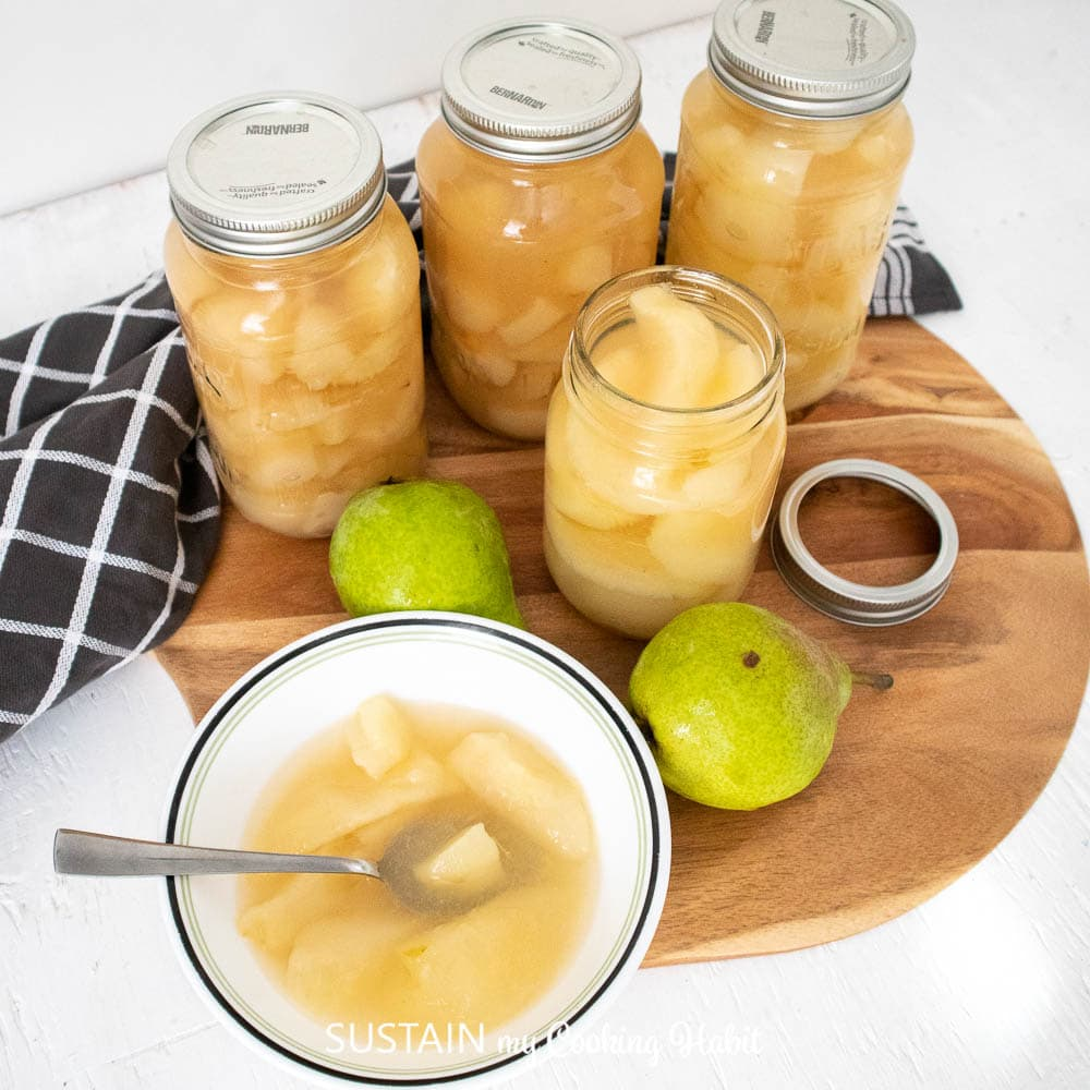 Fresh pairs, canned pear compote and compote in a bowl placed on a serving tray.