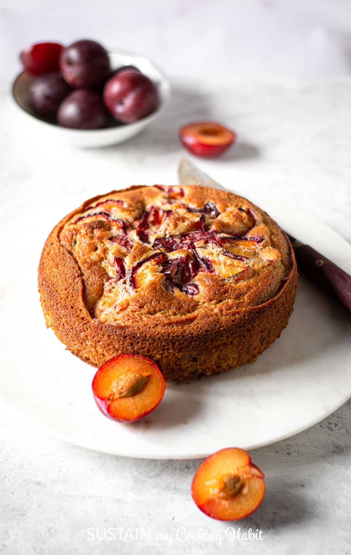 Finished classic plum cake on a plate with fresh plums placed around the plate.