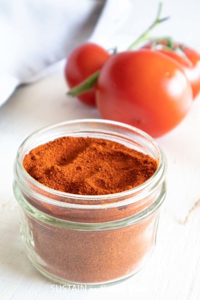 Dried tomato powder in a glass jar next to fresh tomatoes.