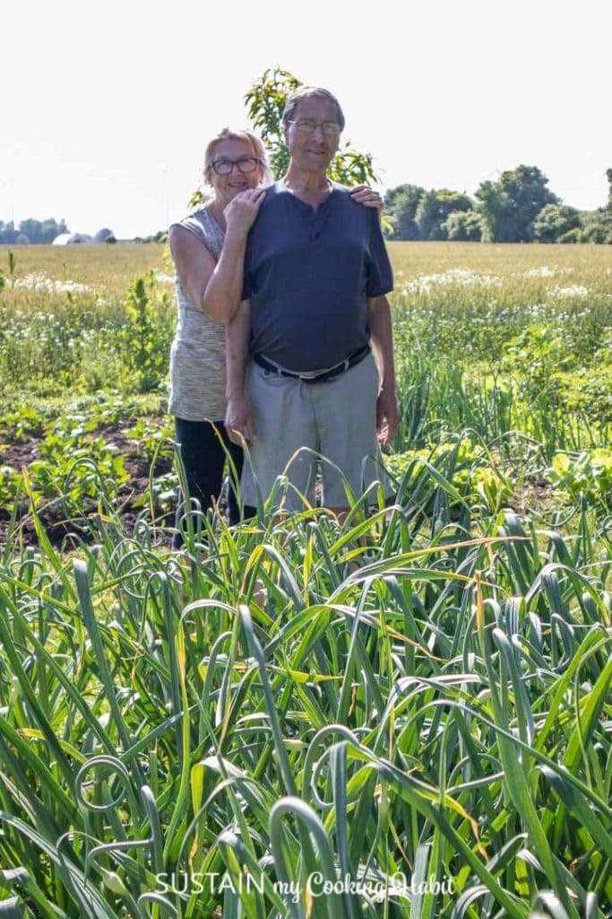 A man and a woman standing near a garden of garlic scapes.