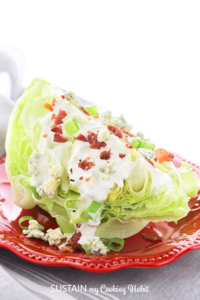 Iceburg wedge salad on a red plate.