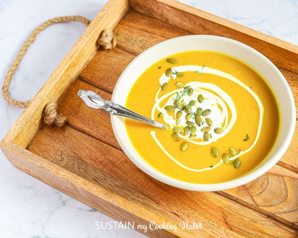 bowl of pumpkin soup on a rustic wood serving tray
