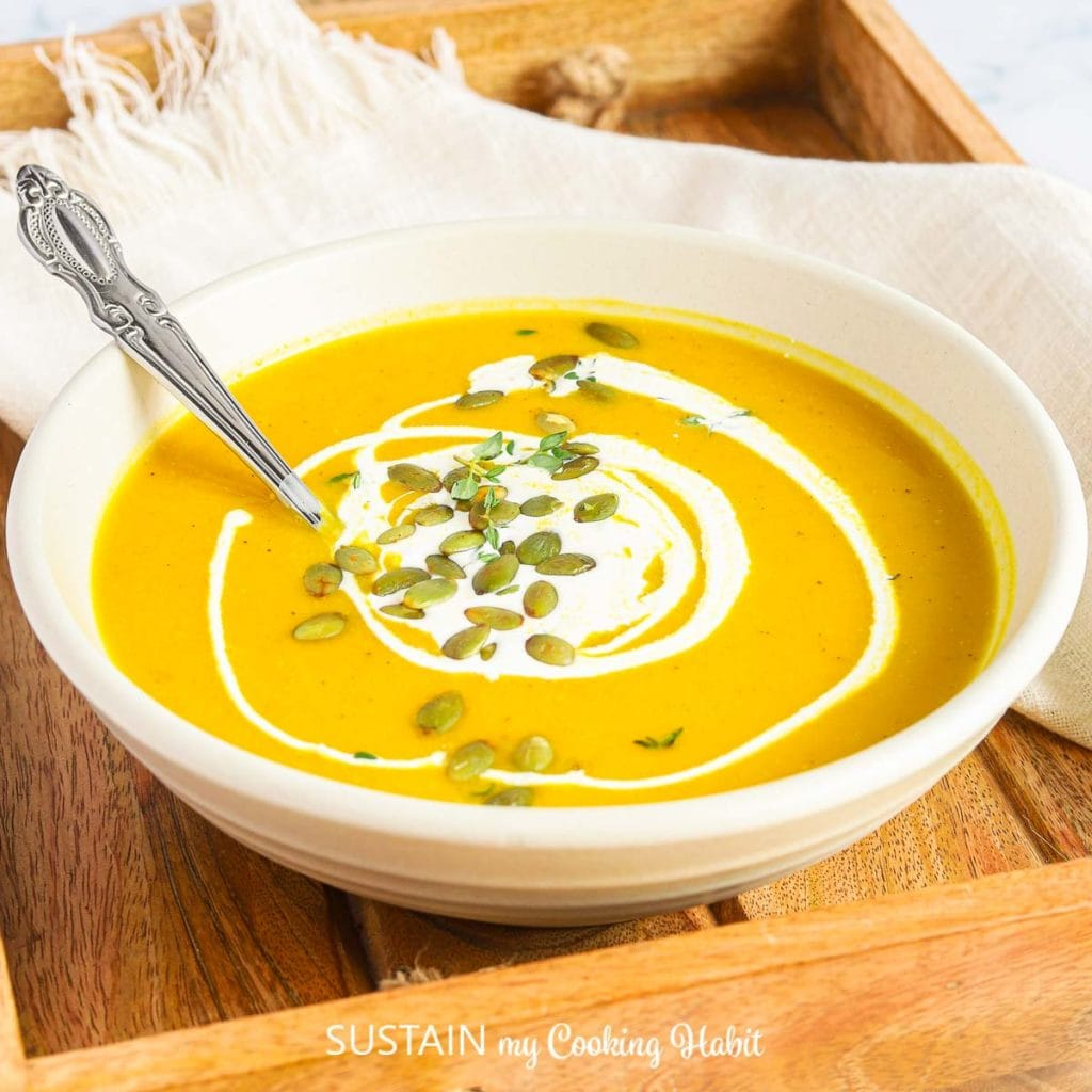 single bowl of warm pumpin soup topped with pumpkin seeds