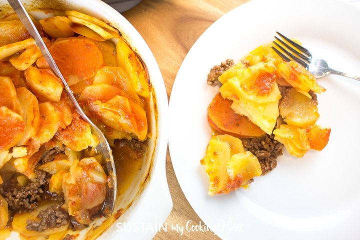 Baked potato and beef casserole in a casserole dish and scooped onto a plate.