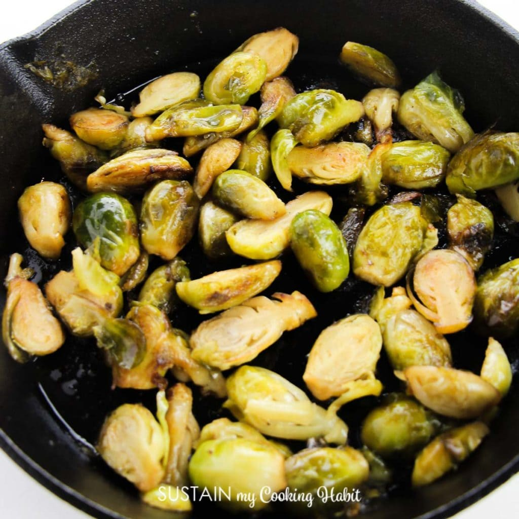 Halved brussel sprouts in a skillet.