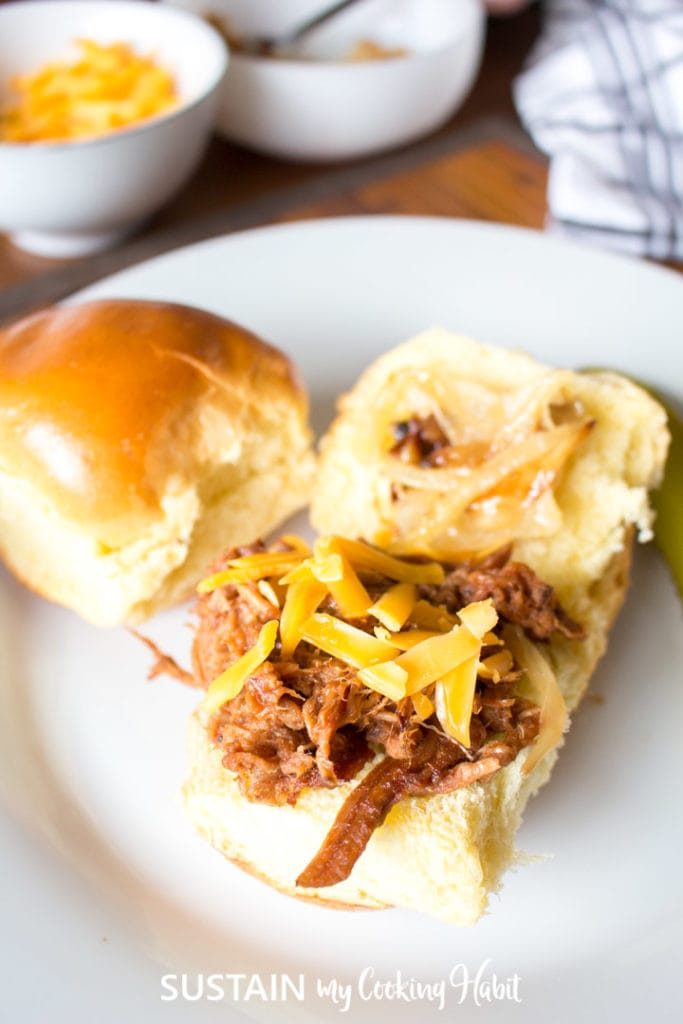 Pulled pork placed on an open bun on a white plate.