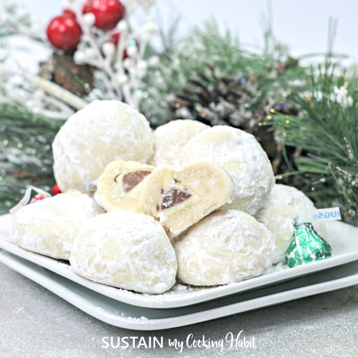 Pile of powdered sugar coated Hershey Kiss cookies on a platter and cut to show chocolate center.