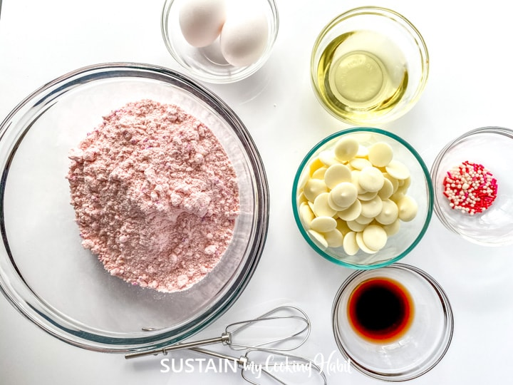 Ingredients needed to make strawberry cake mix cookies placed in glass bowls.