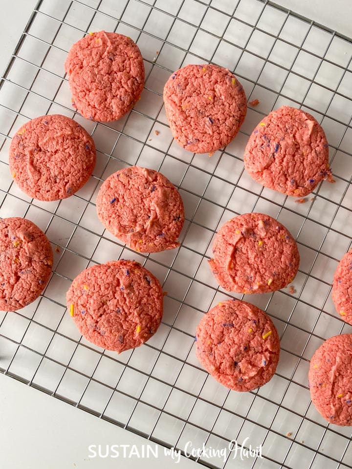 Baked strawberry cake mix cookies placed on a cooling rack.