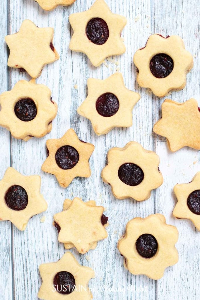 Jam filled Linzer cookies on a wood background.