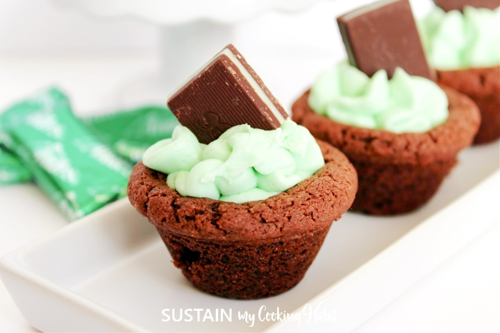 Chocolate mint cookie cup with green frosting and a square of chocolate on top.