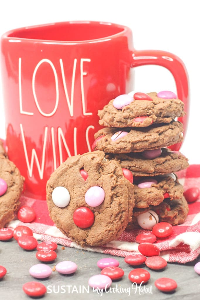 Cookies with M&M candies next to a red coffee cup.