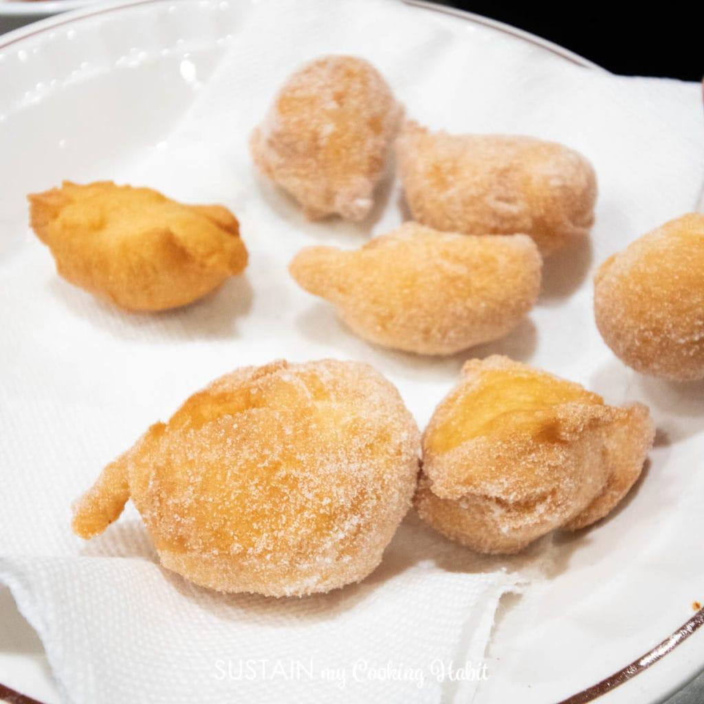 Croatian fritule dipped in sugar.