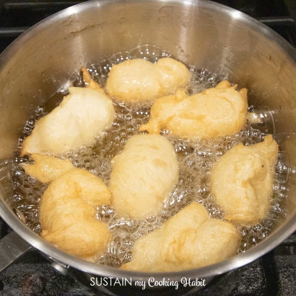 Frying the dough in a pot of oil.