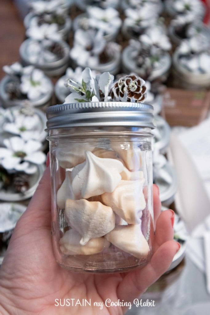 Hand holding a jar of baked meringue cookies.