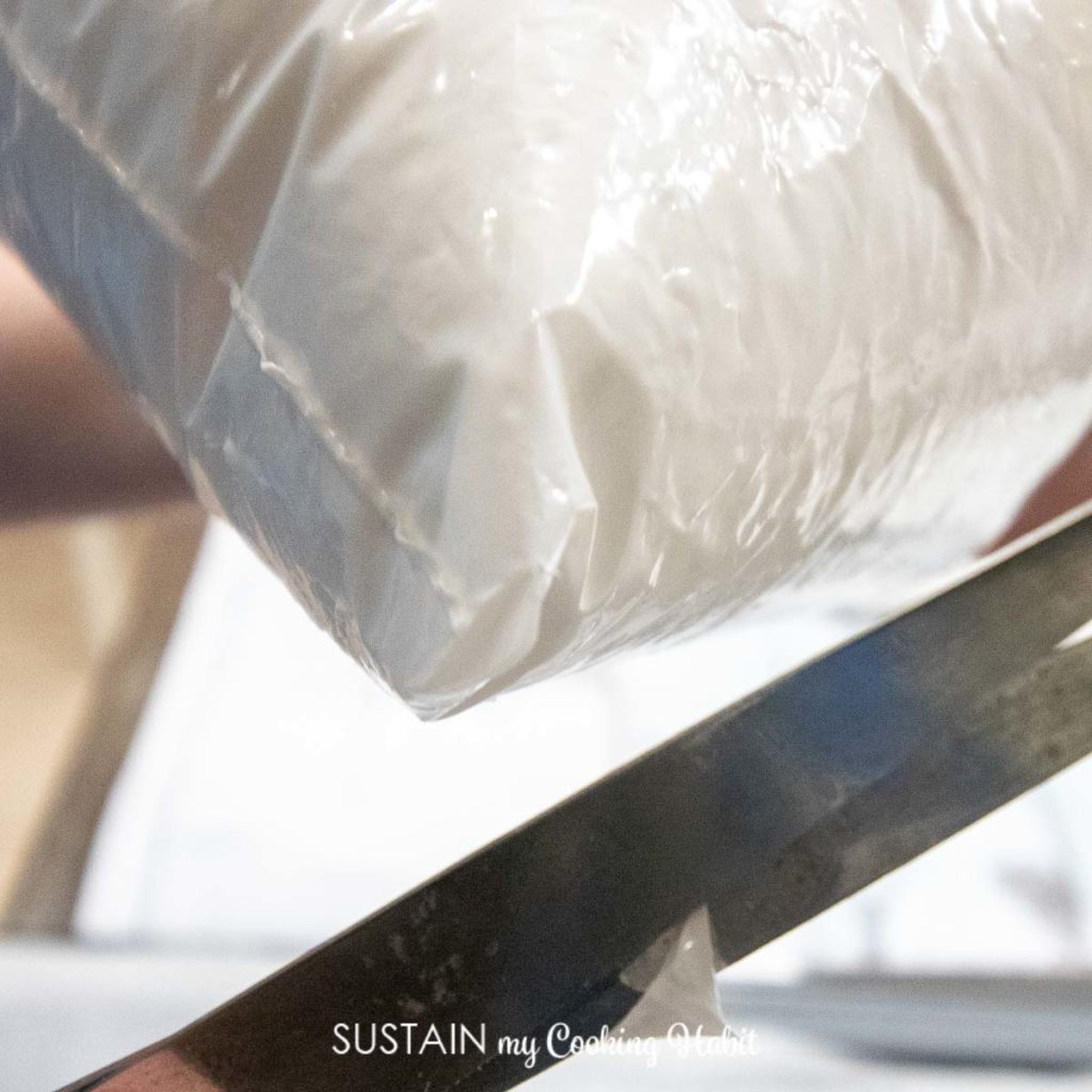 Cutting off the tip of a plastic bag.