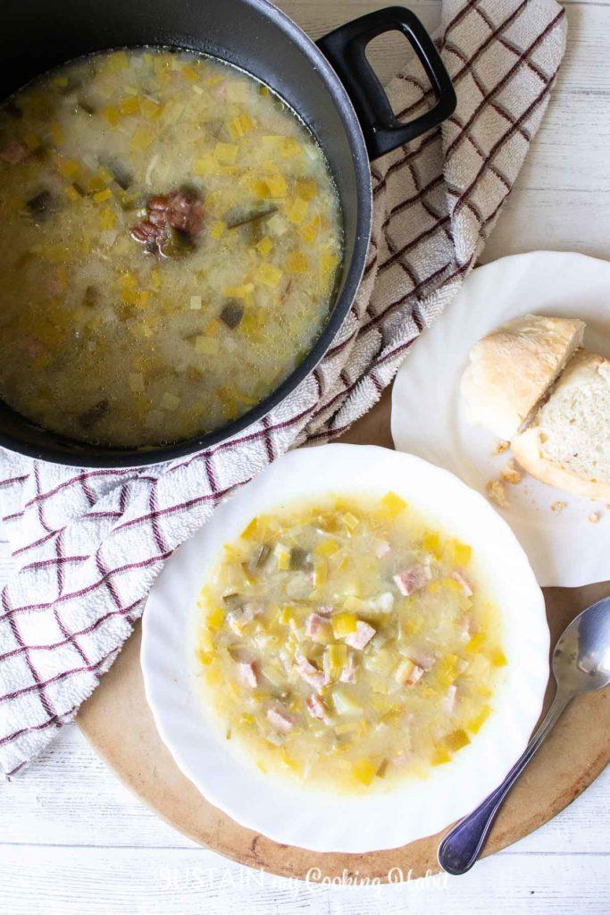 A pot of non creamy potato leek soup next to a bowl of soup and bread.