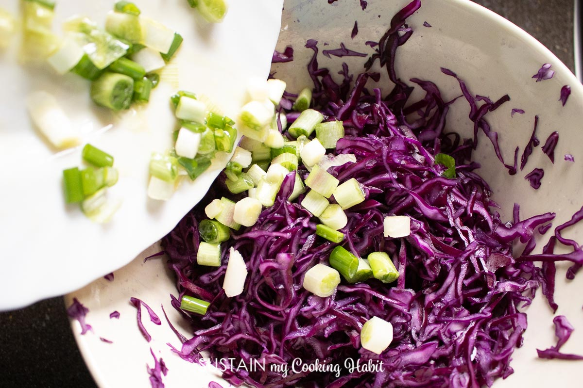 Adding green onions to the red cabbage coleslaw.