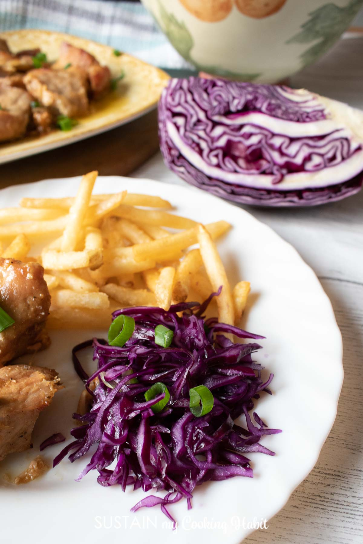 Red cabbage coleslaw served on a plate with chicken and french fries.