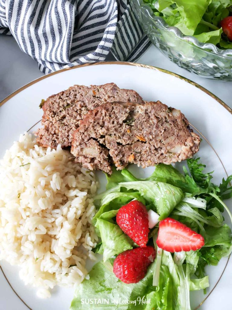 Sliced beef and pork meatloaf next to rice and green salad.