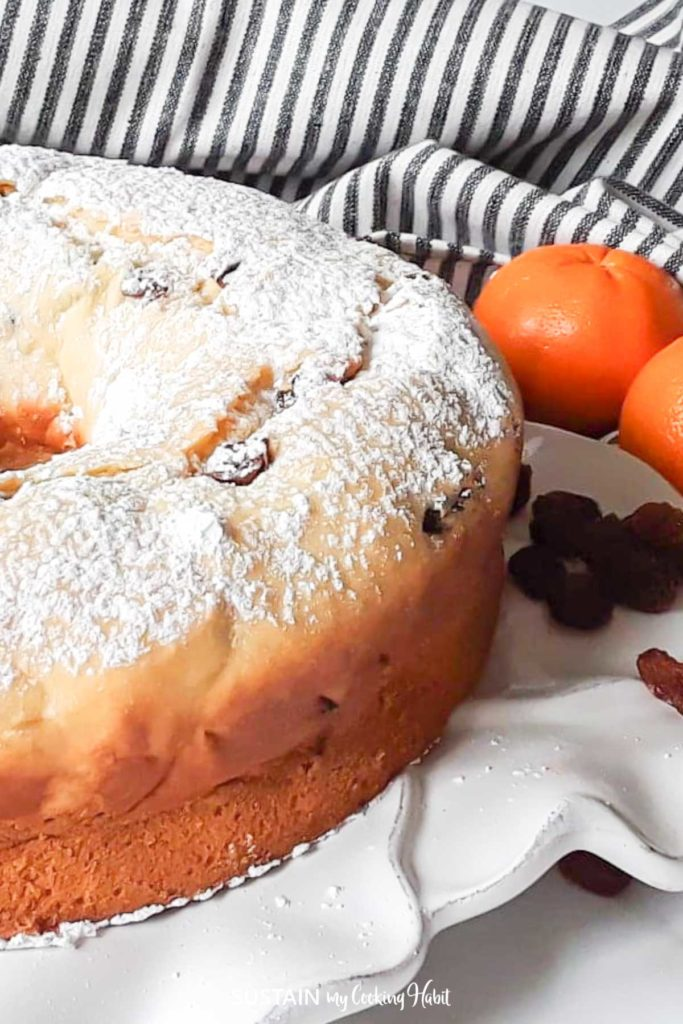 close up of an ornage bundt cake on a platter dusted with powdered sugar