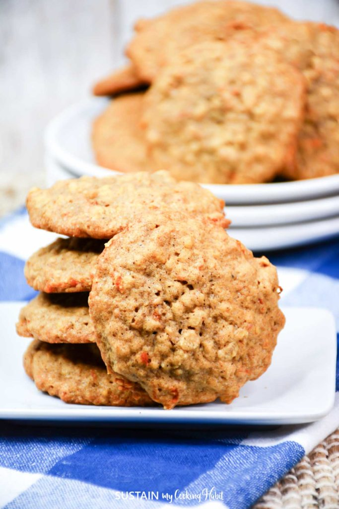 Carrot cake cookies stacked together on a plate.