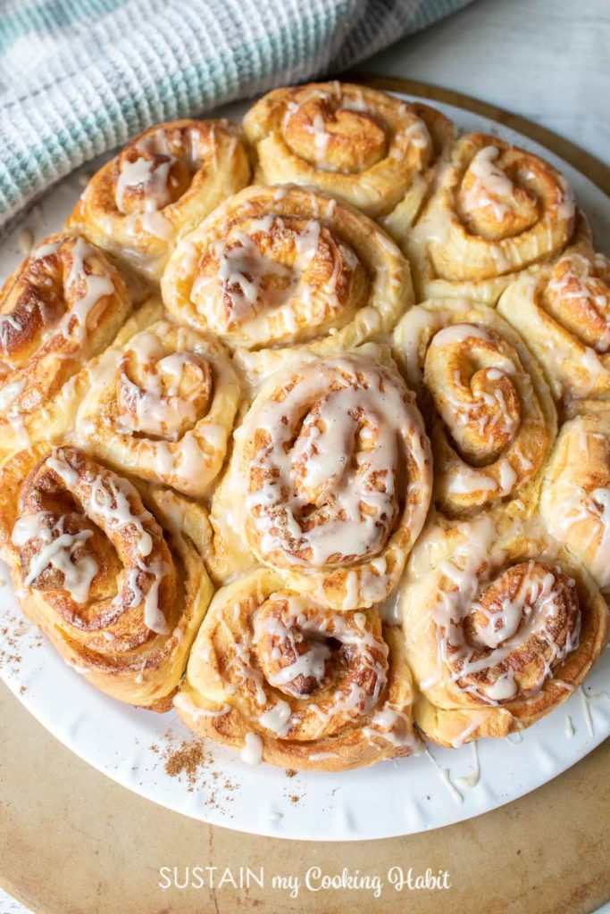 Classic cinnamon buns with icing on a plate.