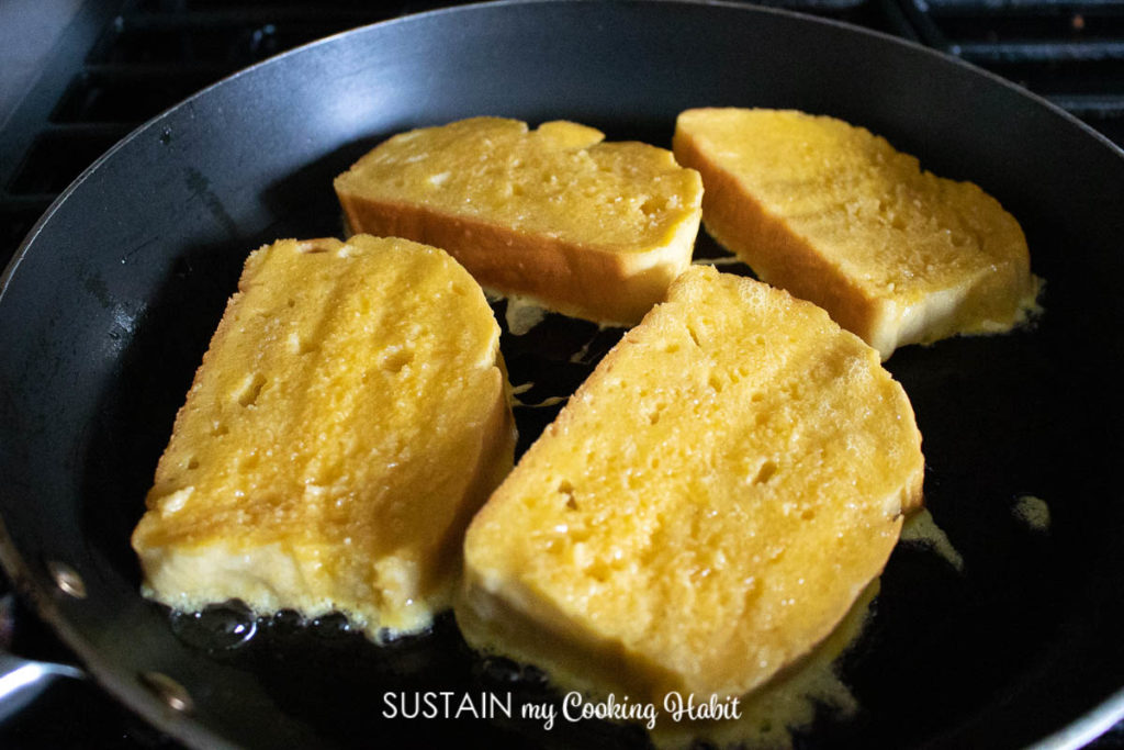 Cooking the dipped egg bread on a pan.