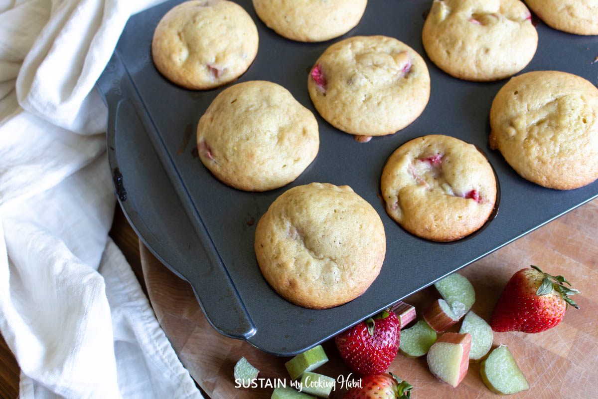 tray of muffins on top of a cutting board with fresh strawberries and rhubarb
