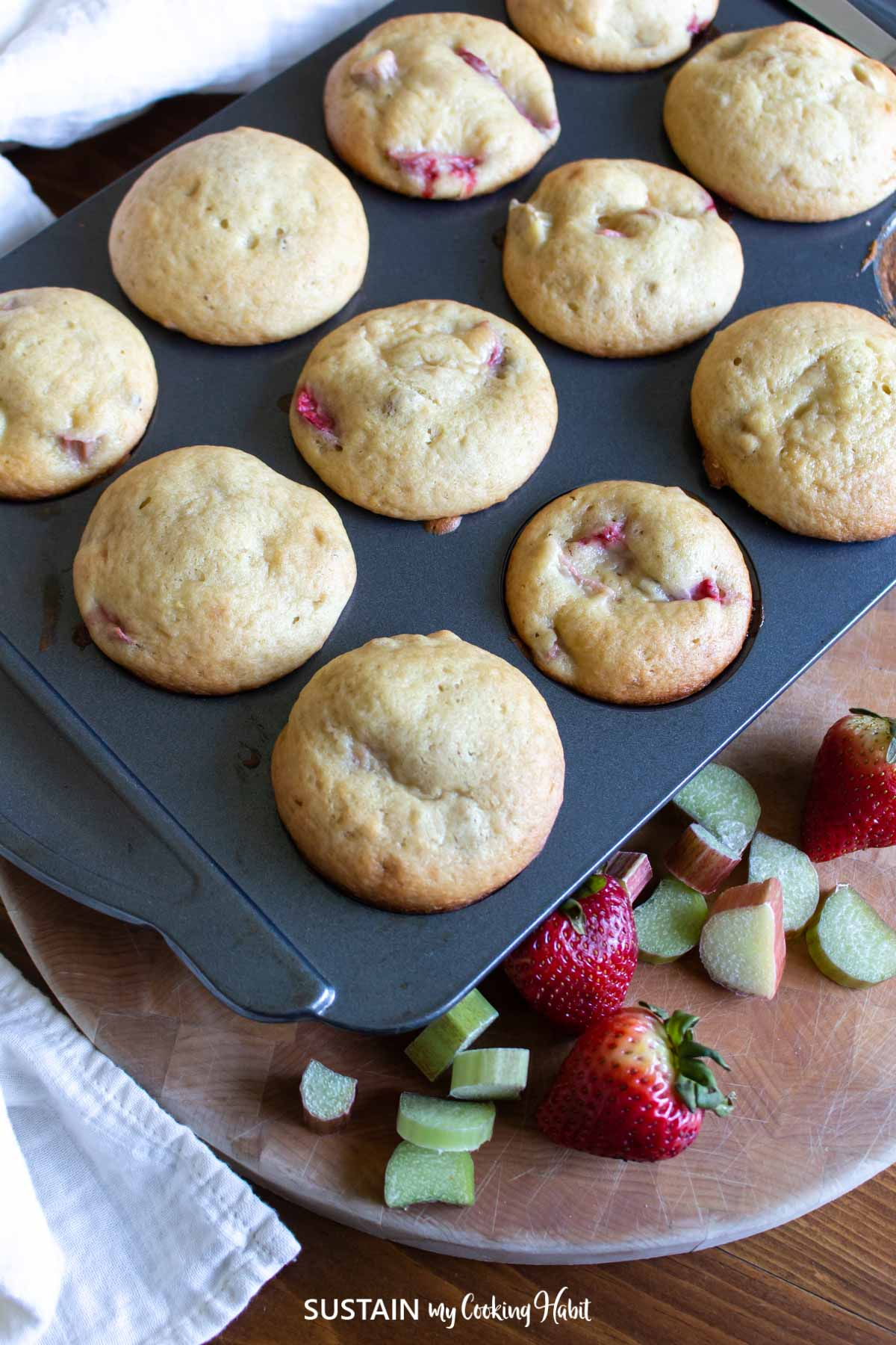Strawberry rhubarb muffins in a muffin tin next to strawberries and cut pieces of rhubarb.