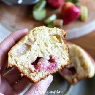 someone holding a strawberry rhubarb muffin cut in half