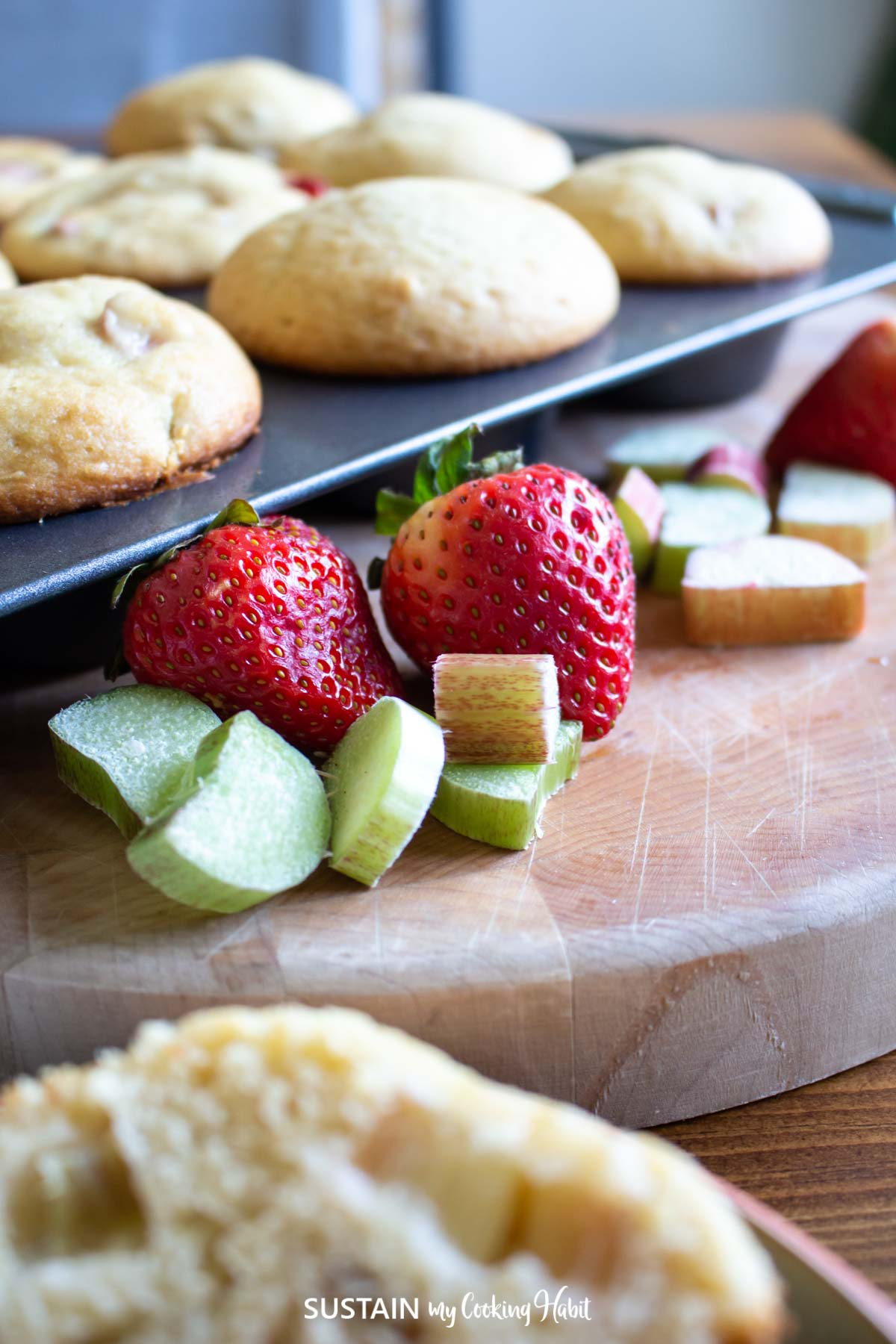 close up image of strawberries and cut rhubarb in front of freshly baked muffins