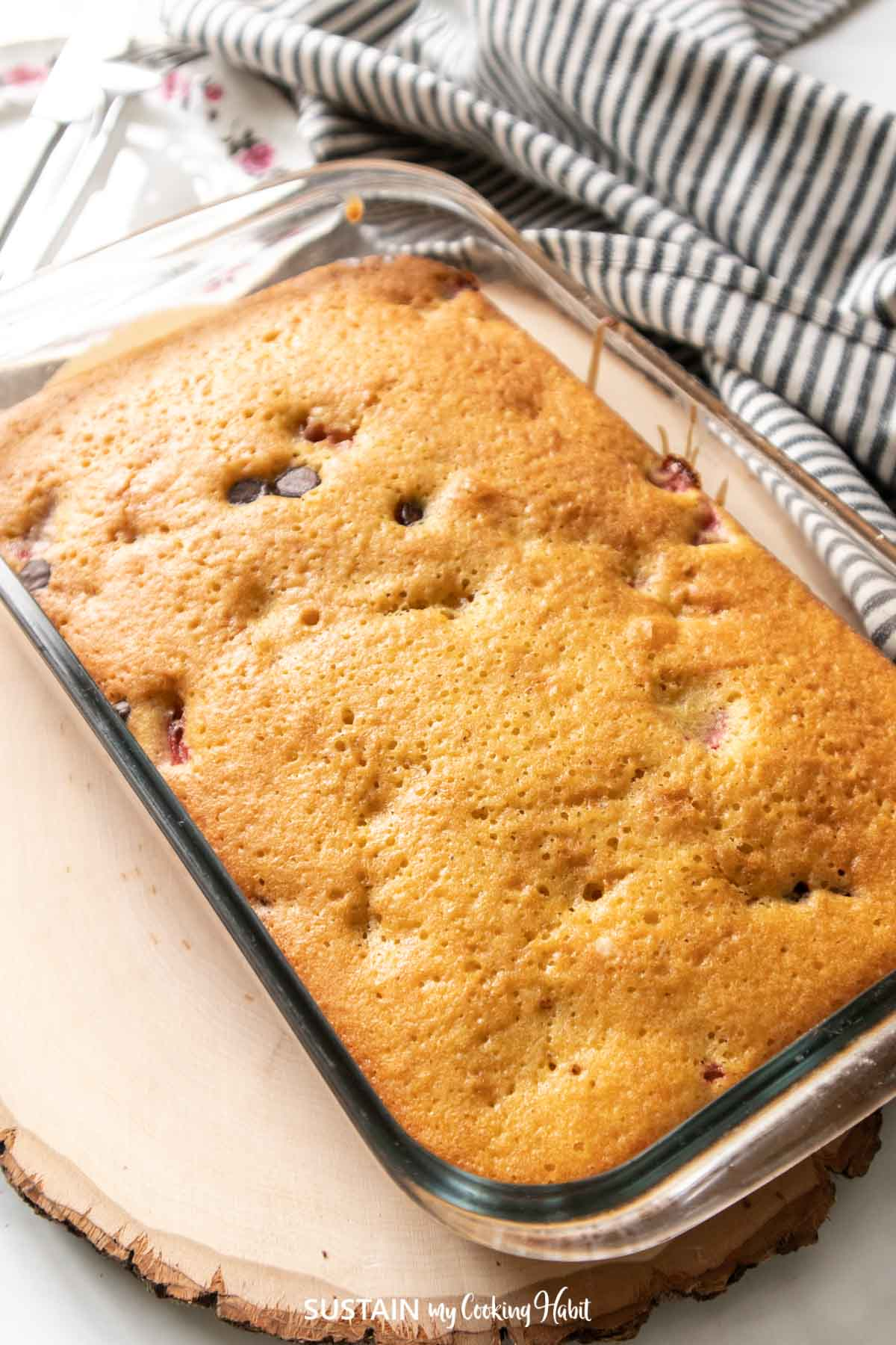Strawberry sponge cake with chocolate chips in a clear pan.