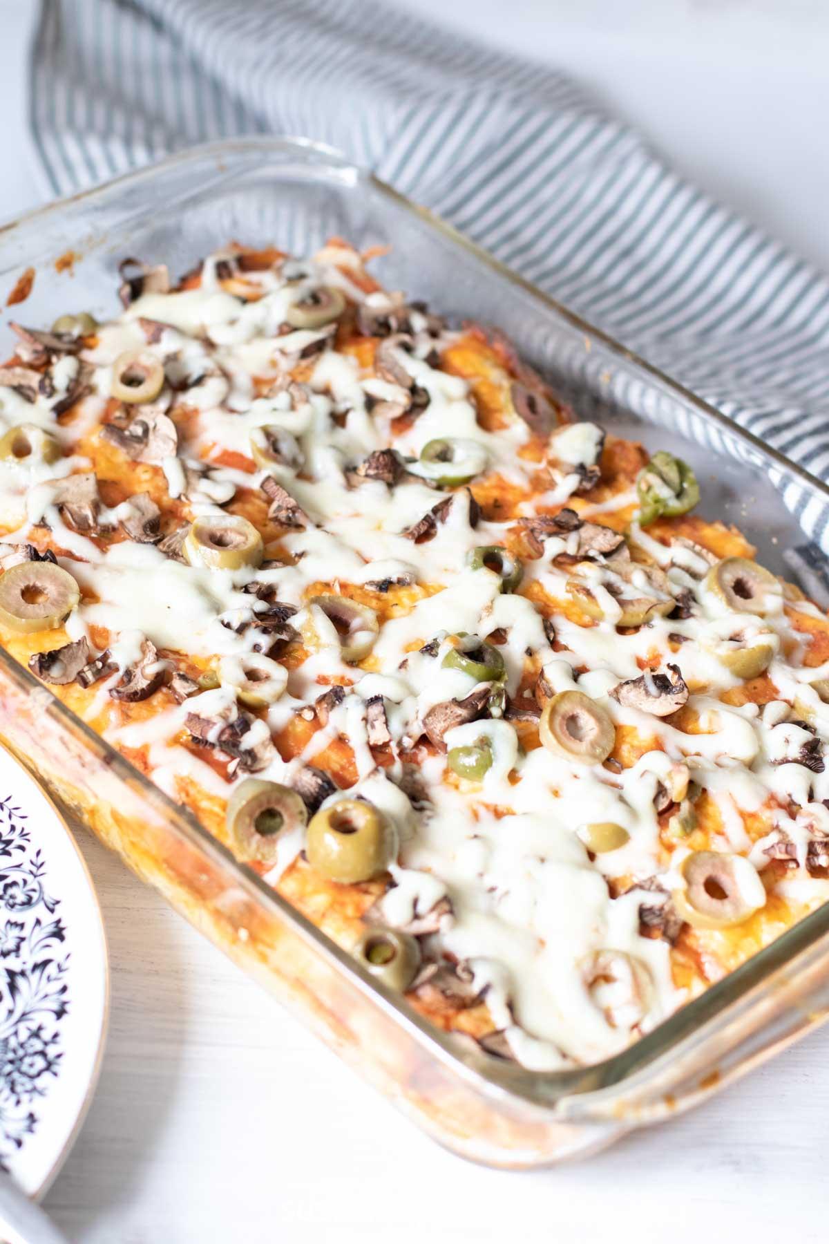 Zucchini pizza in a glass pan.