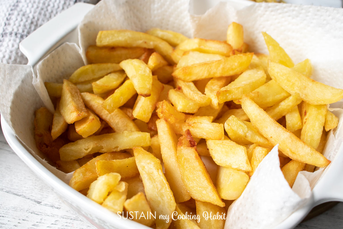 bowl full of freshly made french fries on top of a paper towel