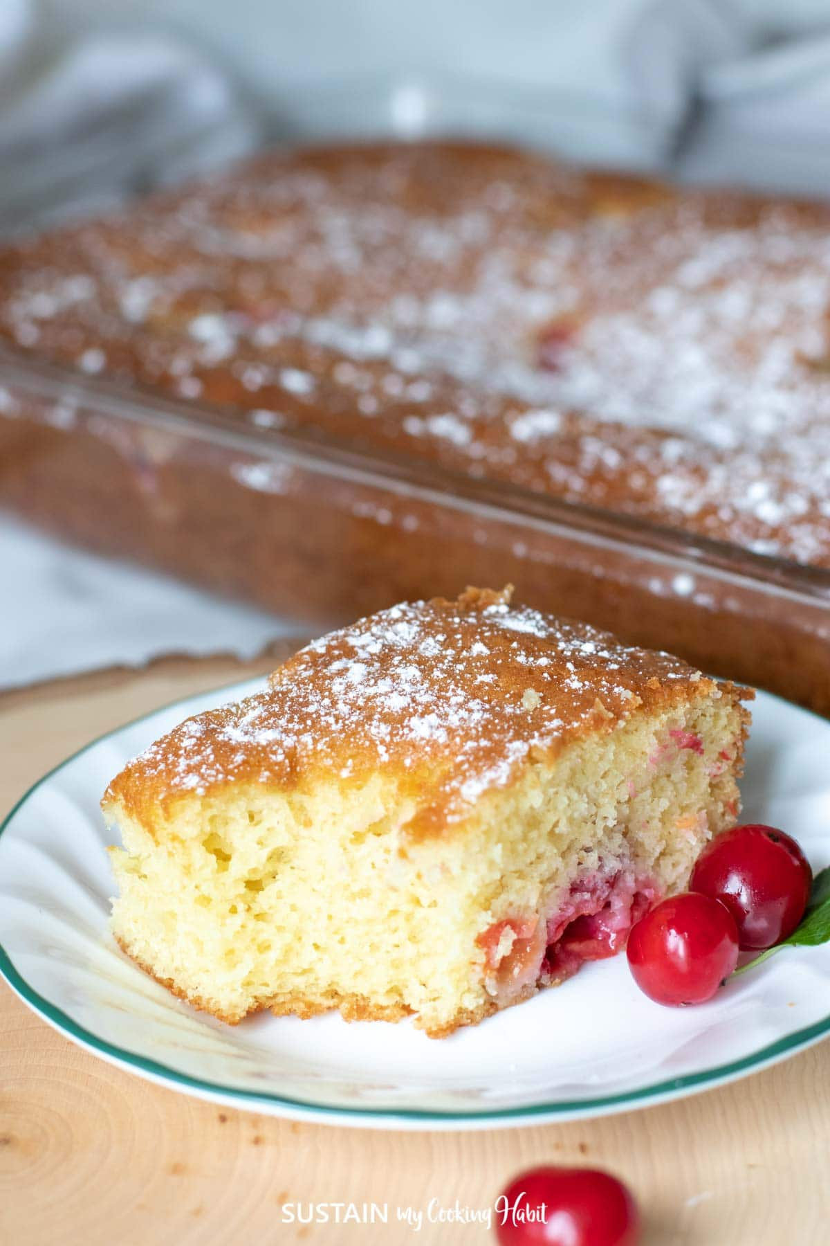 A piece of sour cherry cake next to a glass pan and cherries.