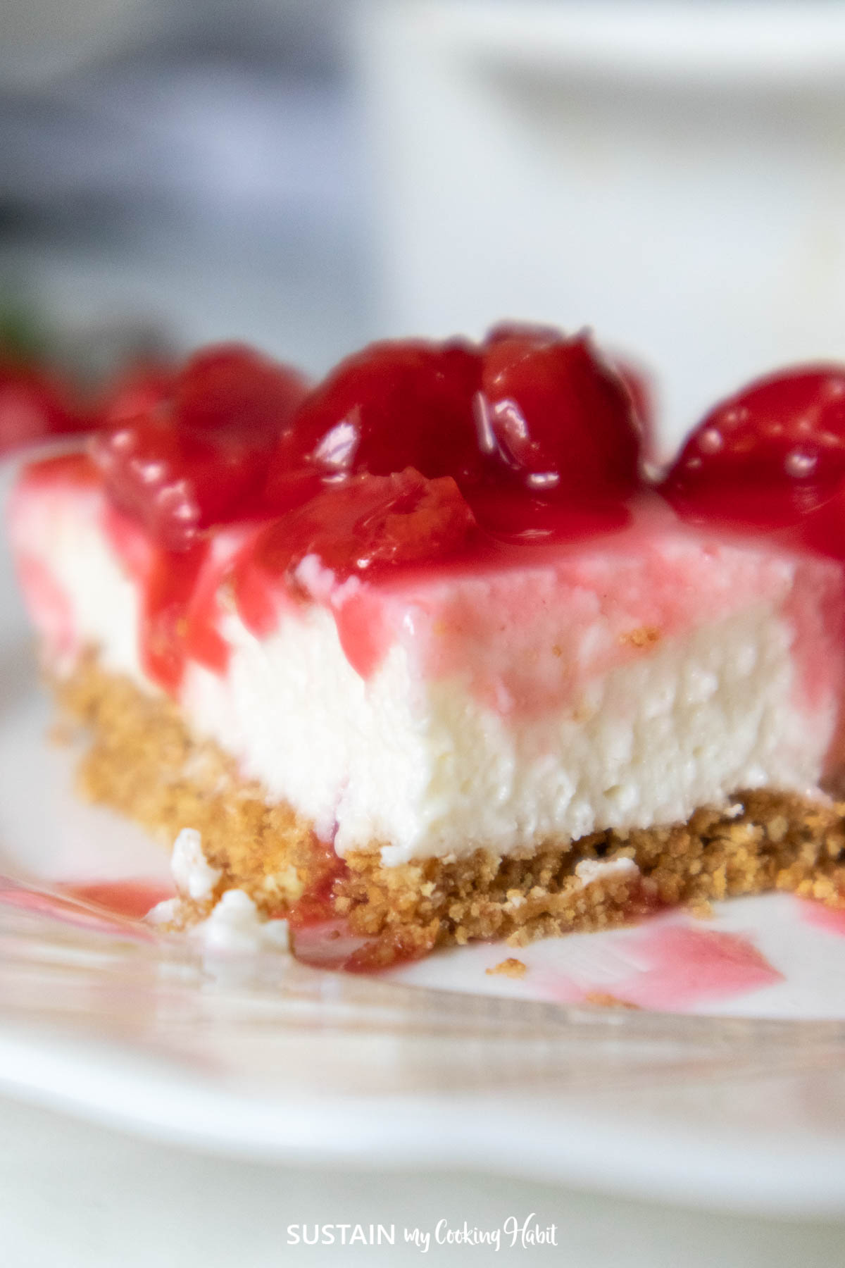 Layers of packed graham cookie crumbs with smooth cream cheese and sour cherry pie filling