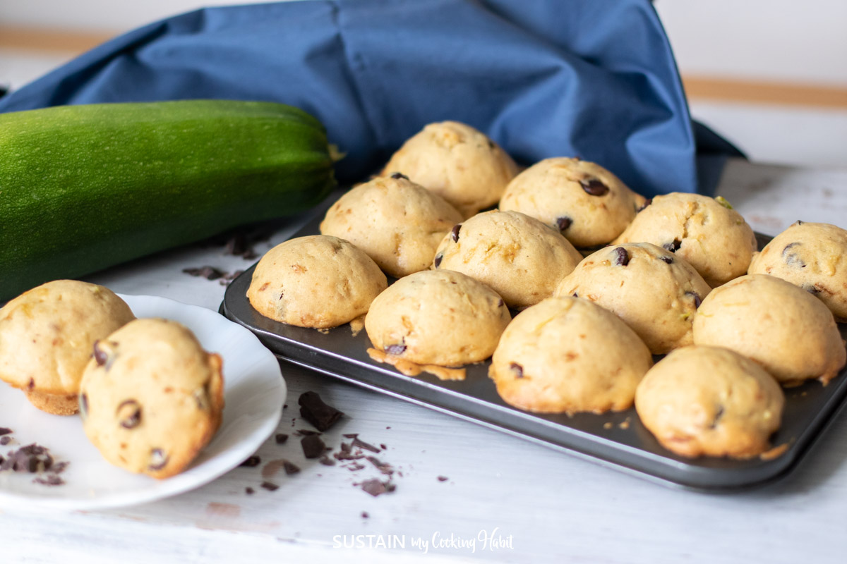 tray full of zucchini muffins with large zucchini in the background
