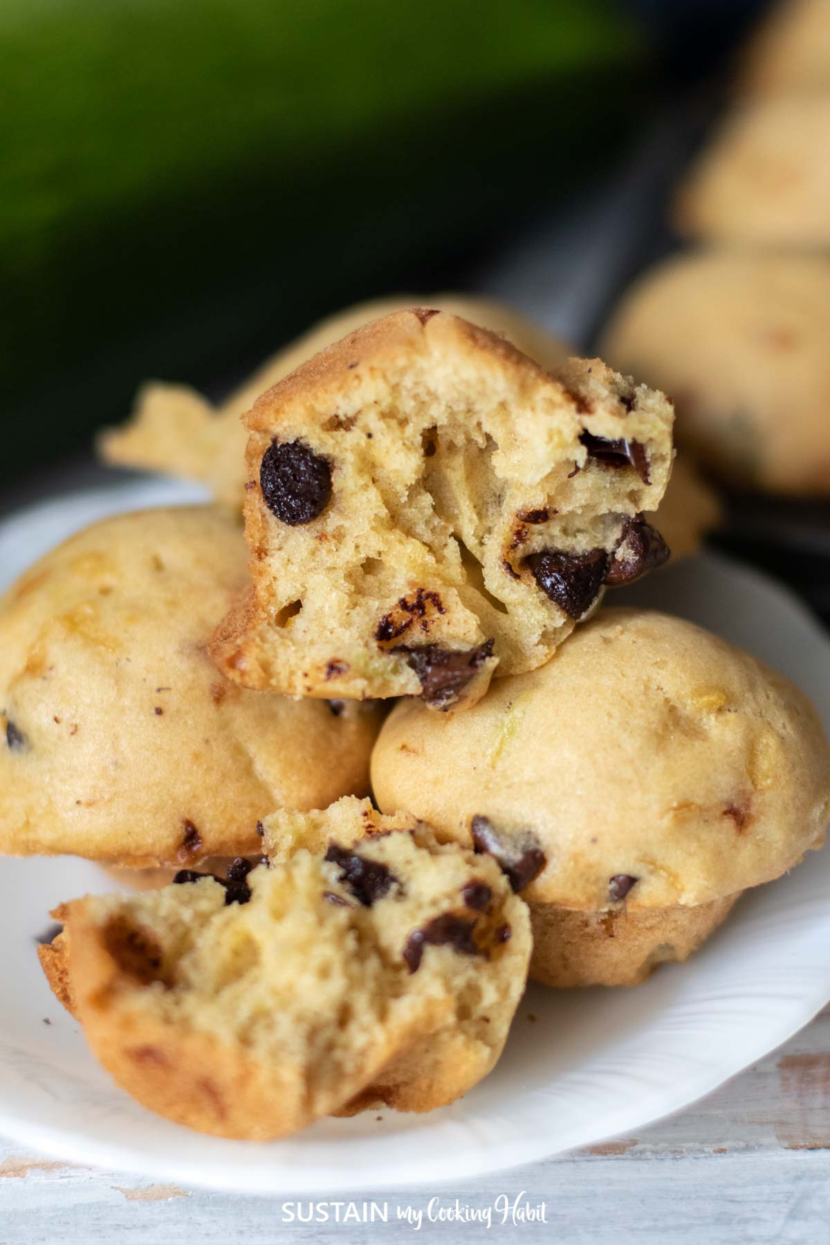 one zucchini muffin cut in half to show the chocolate chips throughout